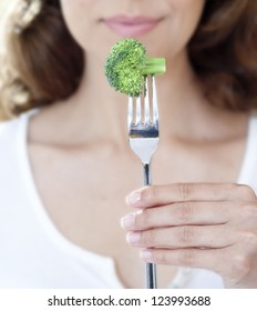 Close-up of woman holding a piece of broccoli on a fork