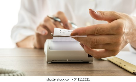 Closeup of a woman holding a printout receipt as it comes out of adding machine while she uses it to make calculations.