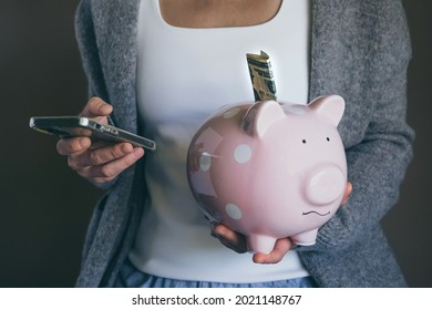 Close-up woman holding sad piggy bank and using mobile phone. Female saving money for household payments, bank bills, calculating monthly family budgets, making investments or strategy for retirement.