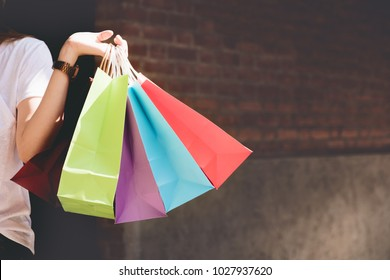 Closeup of woman holding shopping colorful of shopping bags on the street with copy space - Shopping Concept