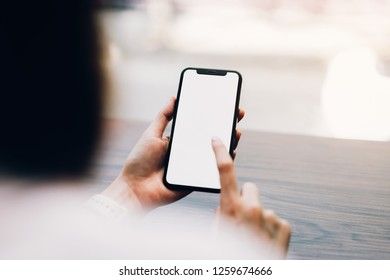 Closeup of woman holding a smartphone, mock up of blank screen. using cell phone in cafe. Technology for communication concept.