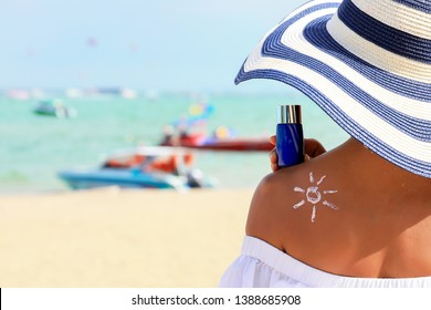Closeup woman holding the sunblock bottle cream in hand, with sunblock lotion cream applied to her back and draw is the sun, at the beach background. Summer or sunblock concept.