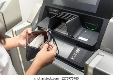 Closeup woman holding the wallet and withdrawing the cash via ATM, business Automatic Teller Machine concept,strain,No money in the pocket