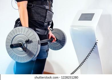 Closeup woman holding weights next to EMS machine