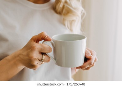 Close-up of a woman holding a white cup of coffee or tea.