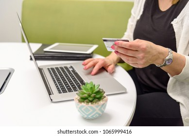 closeup of a woman holdng a credit card at table with laptop computer