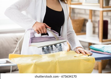 Close-up Of A Woman Ironing Clothes With Steam Emitting From Iron
