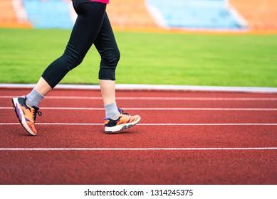 Close-up woman leg running movement on run track in stadium.
