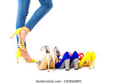 Closeup of woman legs next to many colorful shoes against white backgorund