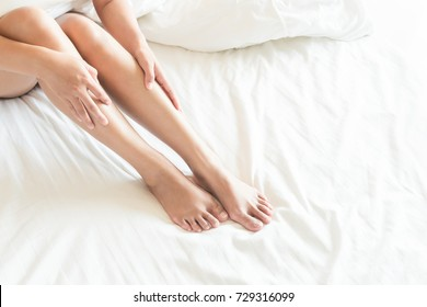 Closeup woman legs on white bed, beauty and skin care concept, selective focus
