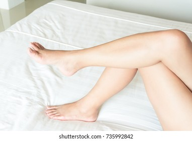Closeup woman legs on white bed with relax feeling, beauty and skin care concept, selective focus