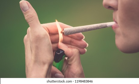 Close-up of woman lighting up marijuana cannabis joint with lighter and big fire. Ready made marihuana/hashish cigarette bought in coffee shop of Amsterdam (Holland - Netherlands)