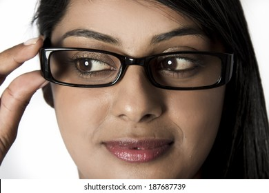 Closeup of woman looking down holding her framed glasses