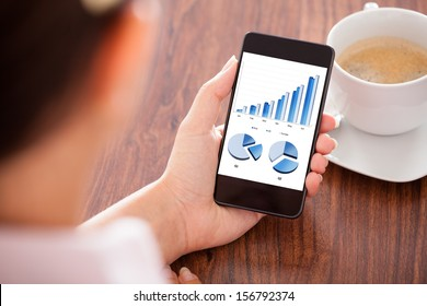 Close-up Of Woman Looking At Graph On Mobile Phone