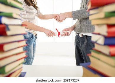 Close-up of woman and man hands is holding diplomas and shaking hands