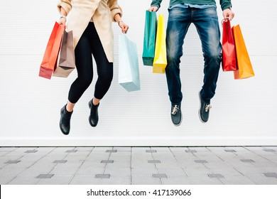 Closeup of woman and man jumping with shopping bags