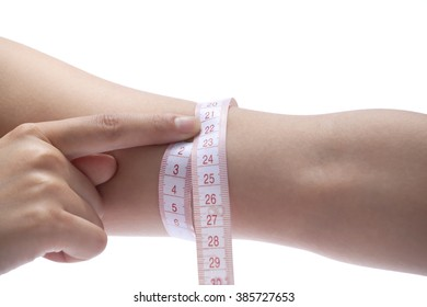 Close-up of woman measuring her arm with measurement tape.