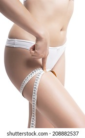 Closeup Of Woman Measuring Her Thigh With Measurement Tape