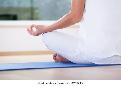 Close-up of woman meditating in lotus position