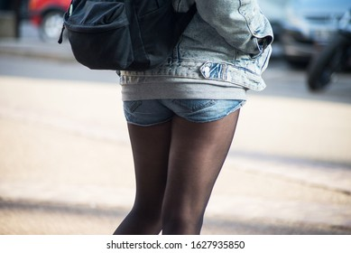 Closeup of woman with mini jeans short standing in the street