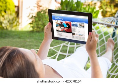 Close-up Of Woman On Hammock Reading News On Her Digital Tablet