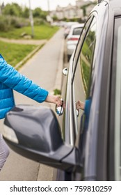 Close-up of woman opening a car door.  hand opening the car door. Chauffeur open car door. Woman Opening door of the modern, new car