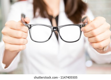 Close-up of woman optician holding trendy and new spectacles