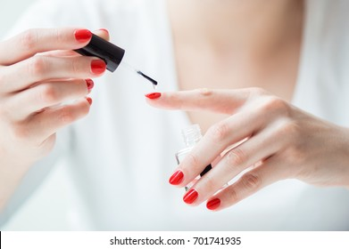 Closeup of a woman painting her nails with transparent nail polish