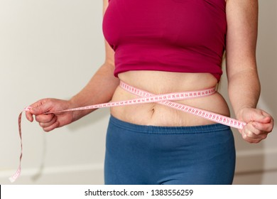 Closeup of woman pinching belly fat. Young slim woman in blue shorts pinching her abdomen. Diet and weight loss concept
