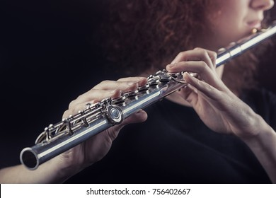 Close-up of a woman playing the flute. Musical concept