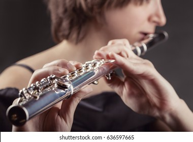 Close-up of a woman playing the flute on black background