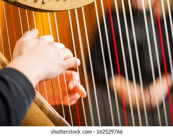 Closeup of a woman playing the harp