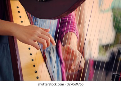 Closeup of a woman playing the harp with soft retro filter effect lighting or instagram filter