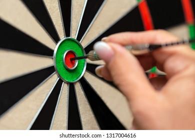 Closeup, woman playing steeldart, professional dart sport trainee, bullseye