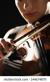 Closeup of a woman playing the violin against black background