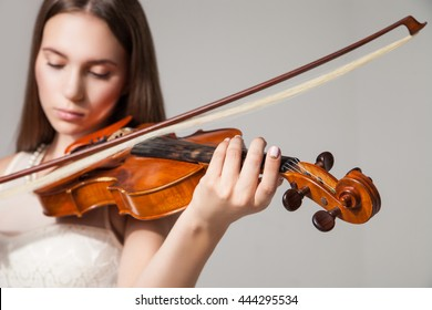 Close-up of woman playing violin with bow