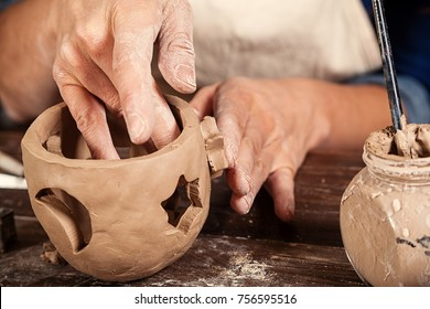 Close-up of a woman potter sculpts a brown clay candlestick  and makes hole in the form of stars for light on the background of a wooden table in the workshop