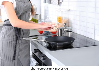 Closeup of woman pouring oil on frying pan