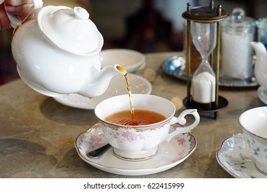 Closeup woman pouring organic tea into the ceramic cup with sand glass - Teapot and Teacup.