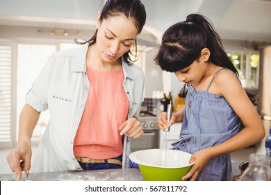Close-up of woman preparing food with daughter at kitchen table