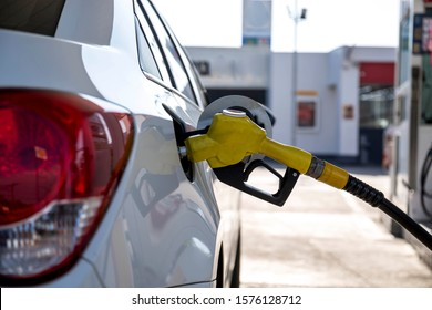 Closeup of woman pumping gasoline fuel in car at gas station. Petrol or gasoline being pumped into a motor vehicle car