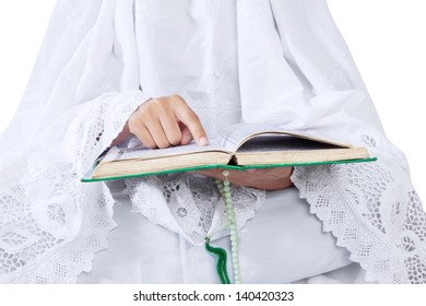 Close-up of woman reading Kuran on white background