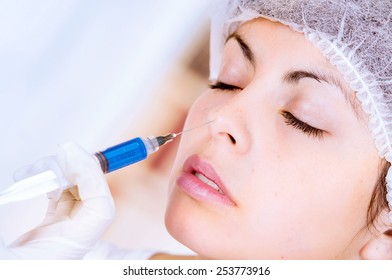 closeup of woman receiving cosmetic injection through nose isolated on white