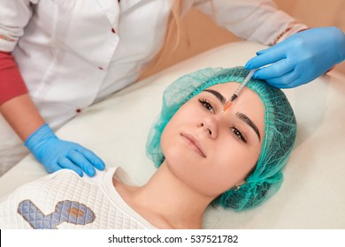 Closeup of woman receiving cosmetic injection through nose.