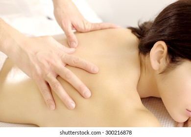 closeup of woman receiving hand massage on her back at beauty spa salon