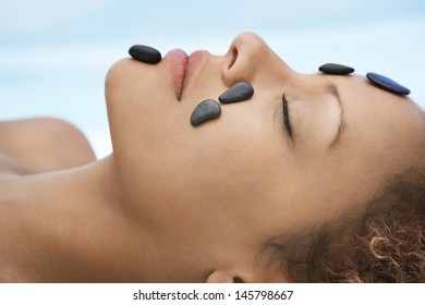 Closeup of woman receiving hot stone therapy on face