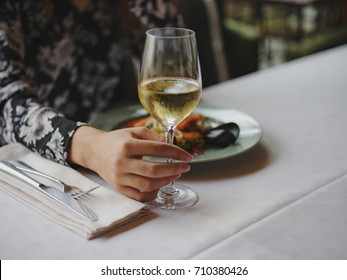 Close-up of a woman at the restaurant. Lady holding wine on a blurred background. Luxurious lunch concept. Copy space.