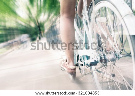 closeup of woman riding by blue vintage city bicycle at the city center with motion blur effect. It is like concept for activity and healthy lifestyle and environmentally friendly transport