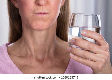 Close-up Of Woman Rinsing And Gargling With Water In Glass