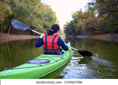 Closeup woman rowing in a green kayak in early autumn along the trees at the bank of Danube river